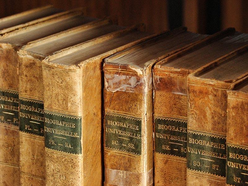Obrázek osmi starých zaprášených encyklopedií v knihovní polici